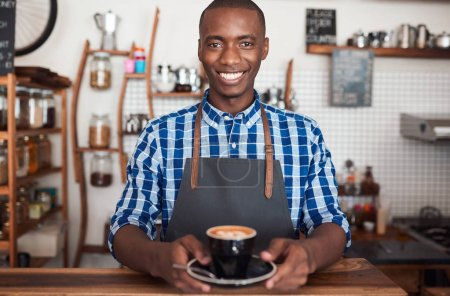 Photo for Portrait of a smiling African barista standing at the counter of a trendy cafe holding a fresh cup of cappuccino - Royalty Free Image
