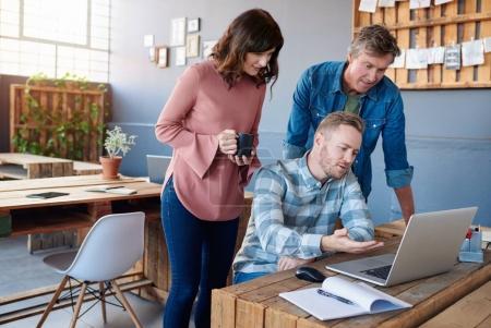 Photo pour Trois jeunes gens d'affaires vêtus de façon décontractée travaillant sur un ordinateur portable et parlant ensemble tout en se tenant à une table dans un bureau moderne - image libre de droit