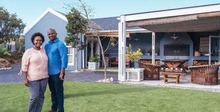 couple standing on backyard of modern home