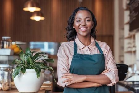 Photo pour Portrait d'un entrepreneur africain femme souriant jeune debout avec les bras croisés dans son café - image libre de droit