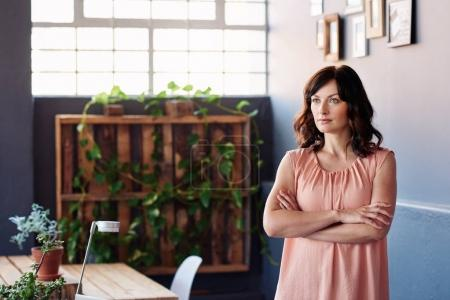 entrepreneur standing with arms crossed in office