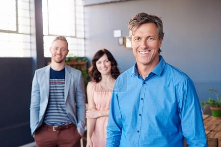 businessman standing in office with colleagues