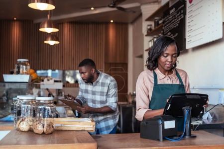 Photo pour Propriétaires de jeunes africains café debout derrière le comptoir de travail avec tablette numérique et écrire dans un cahier à l'intérieur du café - image libre de droit