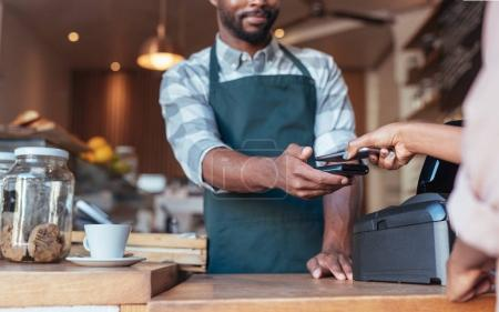 Customer using technology to pay in cafe