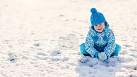 girl sitting on snowy ground outdoors
