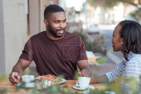 Photo for Smiling young African couple sitting at a table at a sidewalk cafe drinking coffee and talking together while out on a date - Royalty Free Image