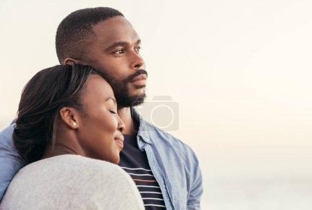 Photo pour Gros plan de contenu jeune couple africains bénéficiant d'une fin d'après-midi ensemble sur une plage au coucher du soleil tout en se tenant dans les bras des uns et des autres - image libre de droit