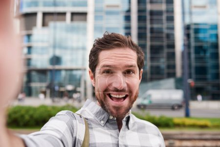 Cheerful young man with beard smiling and taking selfies while enjoying day out in the city