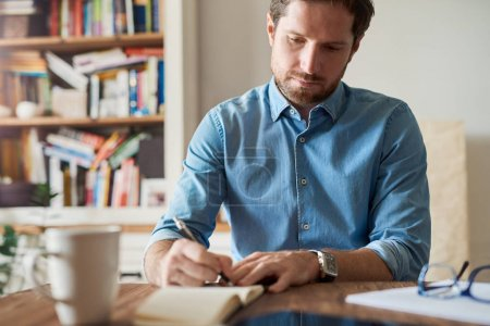 Young man working at home writing ideas down in notebook while sitting alone at table in his living room