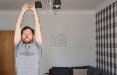 Fit young man in exercise clothing stretching and warming up before working out alone in his apartment