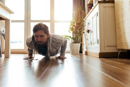 Fit young man in sportswear straining while doing pushups on the floor of his apartment during workout