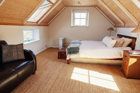 Interior of a comfortable master bedroom with a bed and sofa in the attic of a contemporary residential home