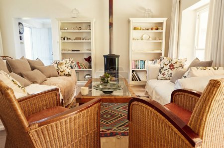 Interior of a country style living room with a sofa, chairs and fireplace in a bright residential home