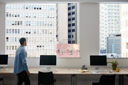 Young Asian designer standing alone by computers in an office looking through the windows at the cityscape