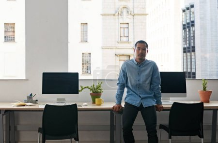 Content young Asian businessman leaning on table by computers in modern office