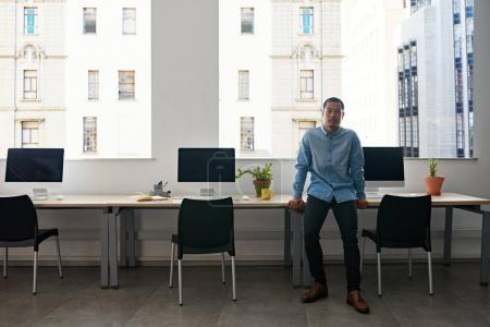 Confident young Asian designer leaning on table by computers in modern office
