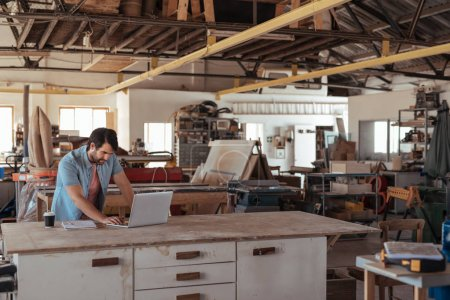 Skilled young woodworker standing at workbench in his large carpentry studio full of carpentry equipment working on new design ideas with a laptop