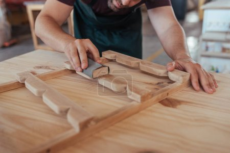 Closeup of carpenter skillfully hand sanding pieces of wooden furniture design while working in his large woodworking shop