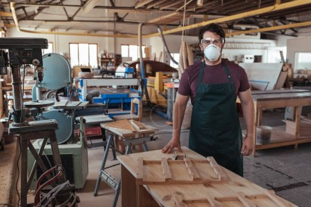 Portrait of a young carpenter wearing an apron and protective mask and glasses standing alone in his large woodworking shop