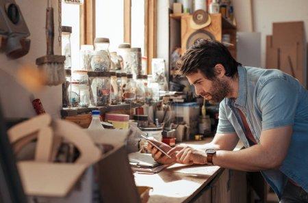 Photo pour Jeune menuisier compétent debout sur un établi plein d'outils dans son atelier de menuiserie à l'aide d'une tablette numérique - image libre de droit
