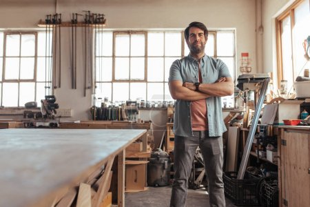 Portrait of skilled young woodworker standing with his arms crossed by workbench full of tools in his carpentry workshop