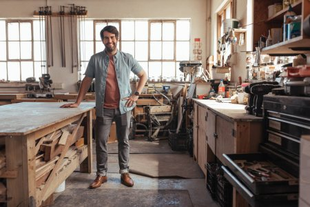 Portrait of young woodworker smiling confidently while standing next to workbench full of wood in his carpentry workshop