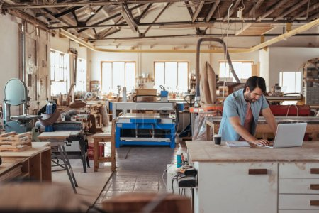 Skilled young craftsman standing at workbench in his large carpentry studio full of woodworking equipment using laptop