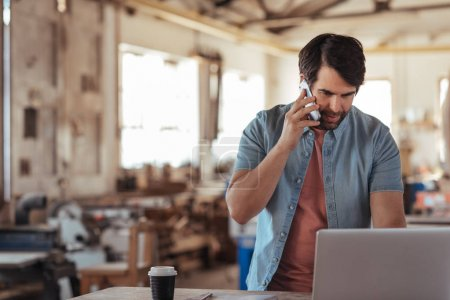 Skilled young craftsman standing at a workbench in his large workshop full of woodworking equipment talking on a cellphone and working on a laptop