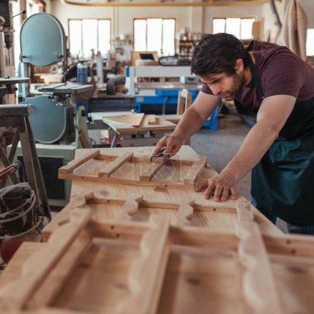 Young craftsman with a beard hand skillfully sanding pieces of a wooden furniture design while working in his large woodworking shop