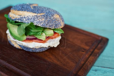 Photo for Closeup of a delicious cream cheese and salmon poppy seed bagel with vegetables resting on a serving board on a rustic turquoise wooden table - Royalty Free Image