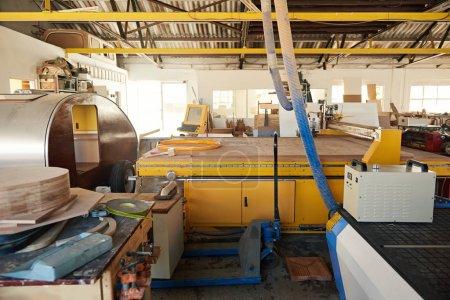 Photo pour Intérieur d'un routeur de grand atelier de menuiserie et d'autres machines industrielles et coupes de bois - image libre de droit