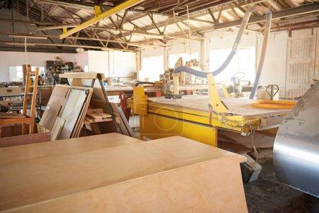 Photo pour Machines et grandes planches en bois assises sur des bancs dans un atelier industriel de menuiserie, avec une torche à l'arrière-plan - image libre de droit