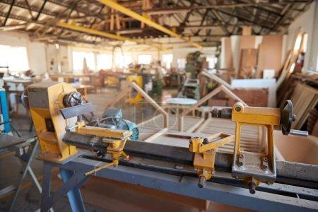 Photo pour Gros tour industriel et autres outils et machines à l'intérieur d'un grand atelier de menuiserie - image libre de droit