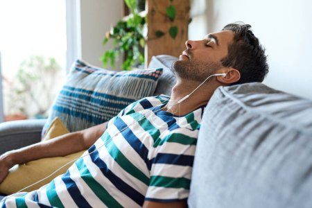 Photo for Young man listening to music on earphones while relaxing alone on his living room sofa with his eyes closed - Royalty Free Image