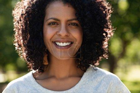 Photo pour Portrait d'une jeune femme souriante aux cheveux bouclés profitant d'un après-midi d'été ensoleillé dans un parc - image libre de droit