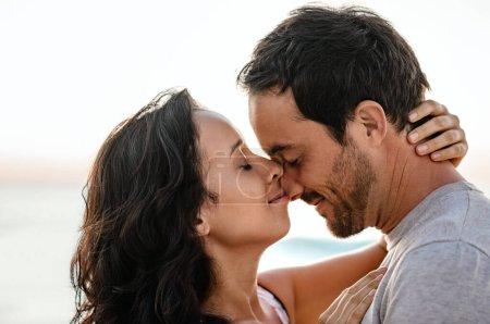 Photo pour Amour jeune couple debout dans les bras de l'autre avec les yeux fermés sur une plage au coucher du soleil - image libre de droit