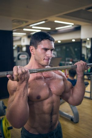 Bodybuilding barbell. At the sports Hall. Man training. Sports. Hard Work. Gym.