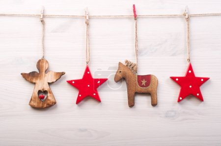 Christmas and New Year wallpaper (background). Christmas toys in a Scandinavian style, such as red stars, a horse and an angel on a white wooden surface.