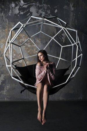schönes junges Mädchen (Frau) mit hellbraunen langen Haaren in einer rosafarbenen Strickjacke, die auf dem Schoß in einem Hängesessel auf dem Hintergrund einer Betonwand sitzt. Halle im Loft-Stil.