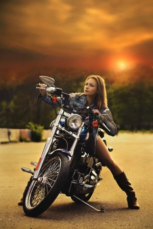 A beautiful slender young woman (girl) sits on a motorcycle against the sunset. Blurred background. Shooting in daylight. Full-length portrait. Concept of leisure and travel on a motorcycle. Concept of leisure and travel on a motorcycle.