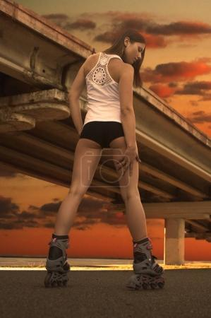 A beautiful young slender girl (woman) with long legs, dressed in a white jersey, shorts and roller skates, stands in the background of the bridge and the setting sun. View from the back. The concept of sport and entertainment. Shooting outdoors.