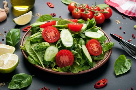 Photo for Low-calorie dietary vegan salad plate on a dark background. Salad from spinach leaves, cherry tomatoes and cucumber slices. Useful dietary dinner.  Vegetarian, vegan concept - Royalty Free Image