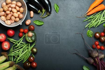 Photo for Vegetable background. Fresh organic vegetables such as carrots, beets, asparagus beans, tomatoes, eggplants, potatoes and corn cobs on a dark surface. Place for text - Royalty Free Image
