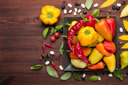 Photo for Autumn background. Yellow and red peppers of different varieties on a square plate. Raw vegetables. Harvest food - Royalty Free Image