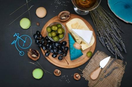 Photo for Cutting board with different types of cheese (blue pesto cheese, aged cheese, brie), olives and grapes on a black background. Next to the flowers of lavender and the sweetness of macaroons. View from above. The concept of loving cheese - Royalty Free Image