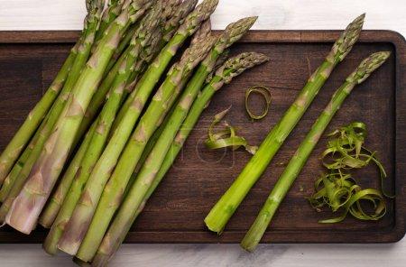 Photo pour Asperges crues sur une planche à découper en bois sur fond blanc. Cadre recadré. Végétarien, concept végétalien - image libre de droit