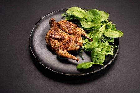Photo pour Caille frite (oiseau) sur plaque d'argile noire, fond noir. De délicieux aliments gastronomiques - image libre de droit