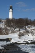 Old Lighthouse Tower Over Beach in Snowy Winter