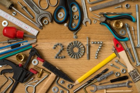Photo for Happy new year 2017 composition with screws, nails,  bolts , dowels and tools on wooden background. New year. New year background. - Royalty Free Image