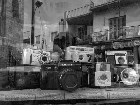An assortment of classic vintage film cameras and flash units di